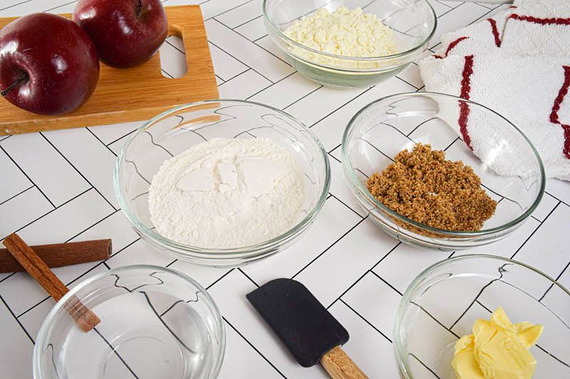 Apple crisp prepped ingredients in bowls on a white background.