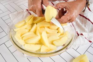 Apples getting sliced into a clear glass bowl.