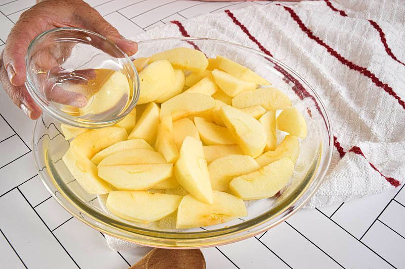 A bowl of sliced apples, white background.