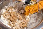 A metal bowl of pumpkin muffin batter.