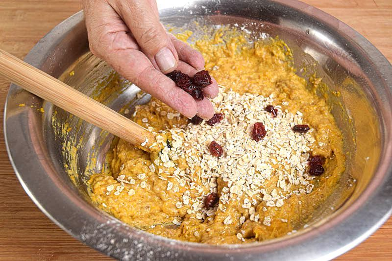 Pumpkin Muffins with cranberries batter in a metal bowl, a hand sprinkling in the cranberries.