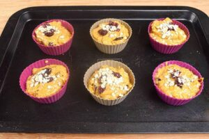 Pumpkin Muffins with cranberries in silicone muffin molds on a baking sheet.