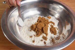 A metal bowl of pumpkin muffin batter being made.
