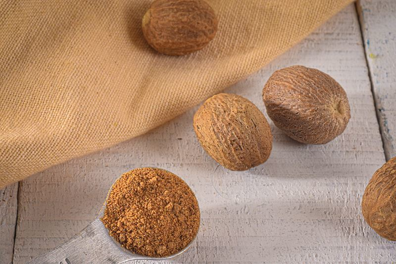 Ground nutmeg in a measuring spoon, whole nutmeg on the side.