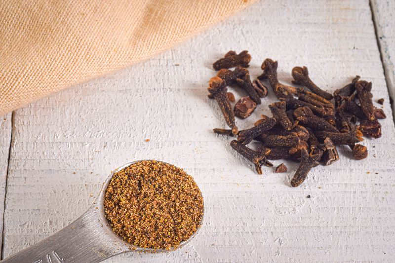 Ground cloves in a measuring spoon, whole cloves on the side.