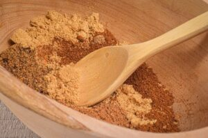 A wooden bowl full of pumpkin pie spice mix and a small wooden spoon.