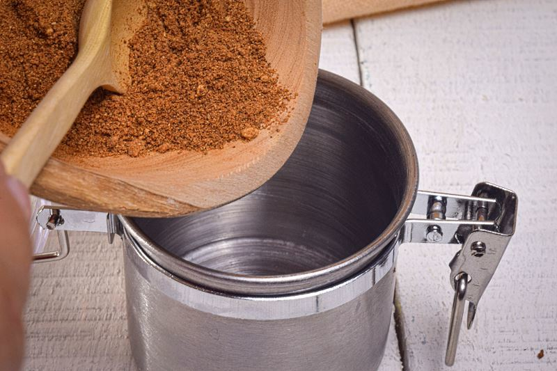 Pumpkin pie spice getting transferred from wooden bowl to metal canister.