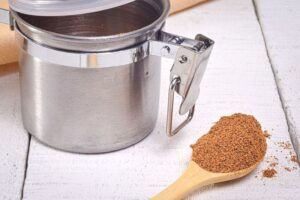 Pumpkin pie spice on a wooden spoon, metal canister in the background.