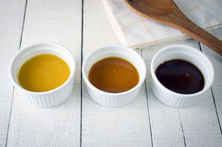 3 colors of roux in ramekins on white wooden background.