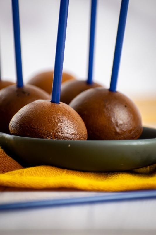 Chocolate cake pops upside down on a dish with blue treat sticks, yellow cloth underneath.