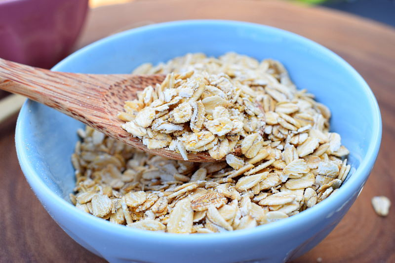 A spoon in a blue bowl of rolled oats.