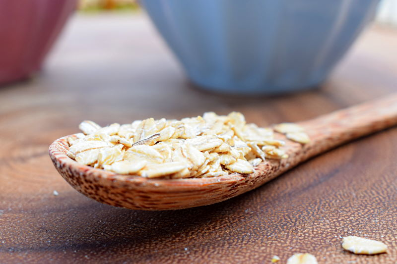 A spoon of rolled oats on wooden background.