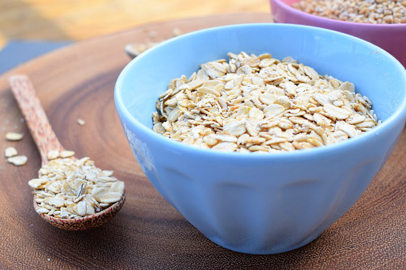 Rolled oats in a blue bowl, and a spoon of oats on a wooden board.