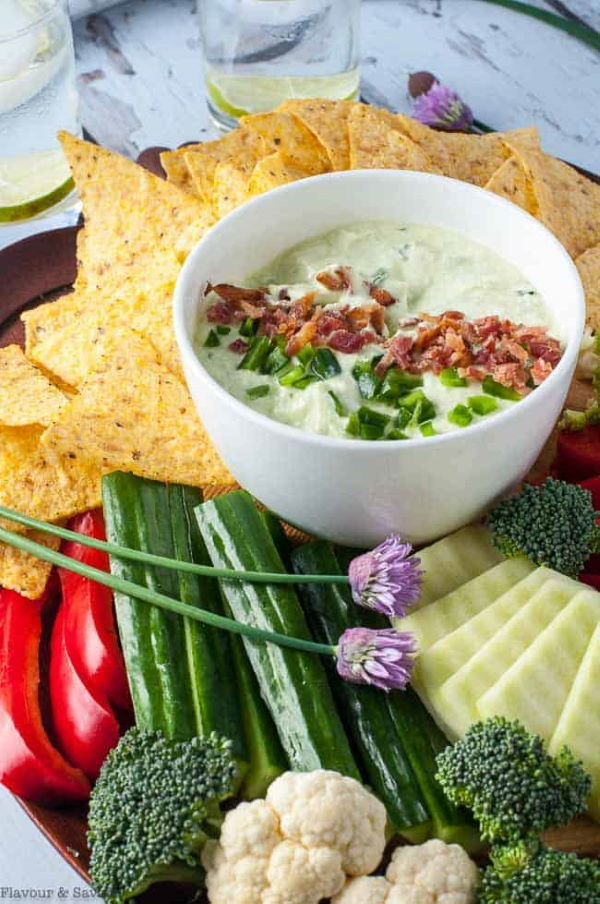 Bacon and chive jalapeno dips in a small white bowl, tortillas and vegetables for dipping on the side.