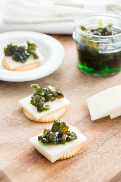 Candied jalapenos on cheese and crackers, wooden background.