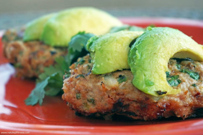 Chicken jalapeno burgers with slices of avocado on top, on a red plate.