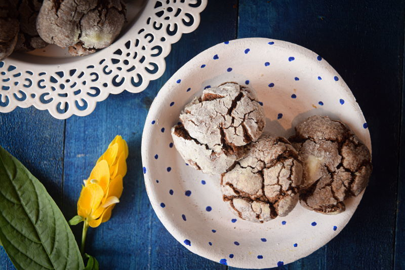 Chocolate crinkle cookies on a white plate, with yellow flowers on the side, blue background.