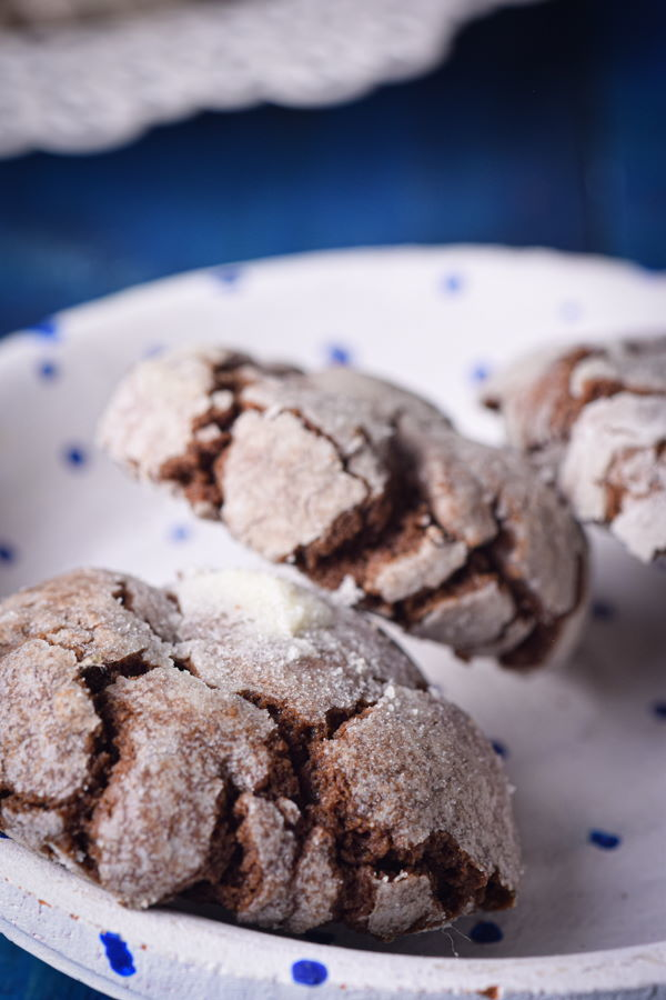 Chocolate crinkle cookies on a white plate, blue background.