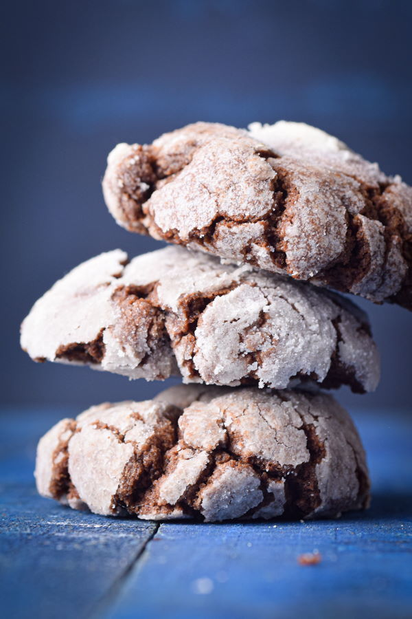 Chocolate crinkle cookies stacked up, blue background.