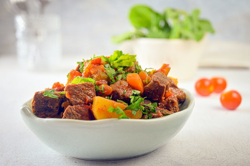 Electric Skillet Beef Stew in a white bowl, cherry tomatoes on the side, white background.