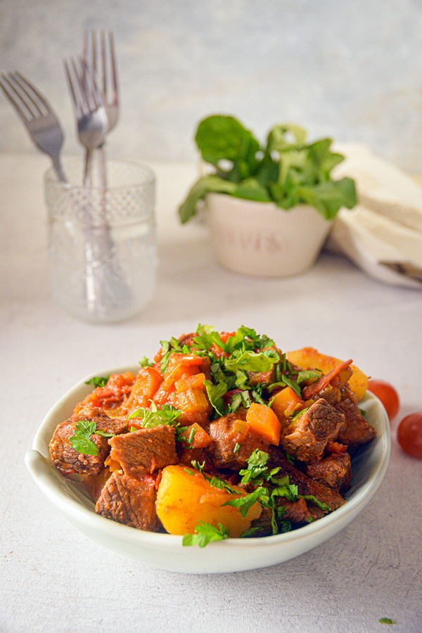 Electric Skillet Beef Stew in a white bowl, cherry tomatoes and forks on the side, white background.
