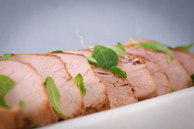 Sliced pork tenderloin in a white rectangular dish.