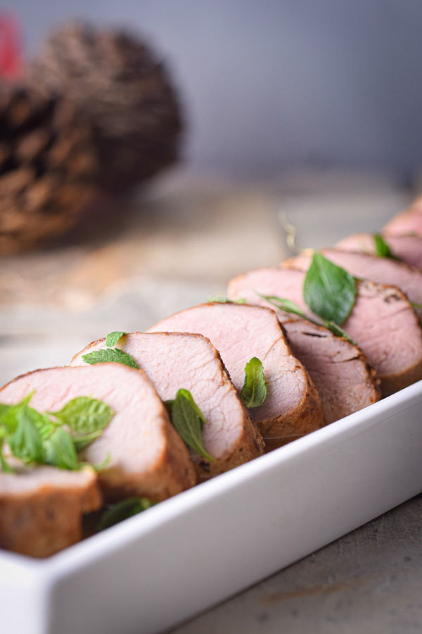 Sliced pork tenderloin in a white rectangular dish.