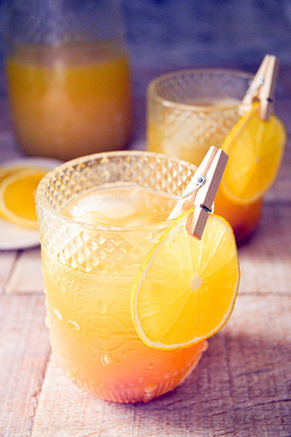 Fall Pumpkin Party Punch in a clear glass with a thin orange slice garnish clipped on with a clothespin, glass pitcher of punch in the background.