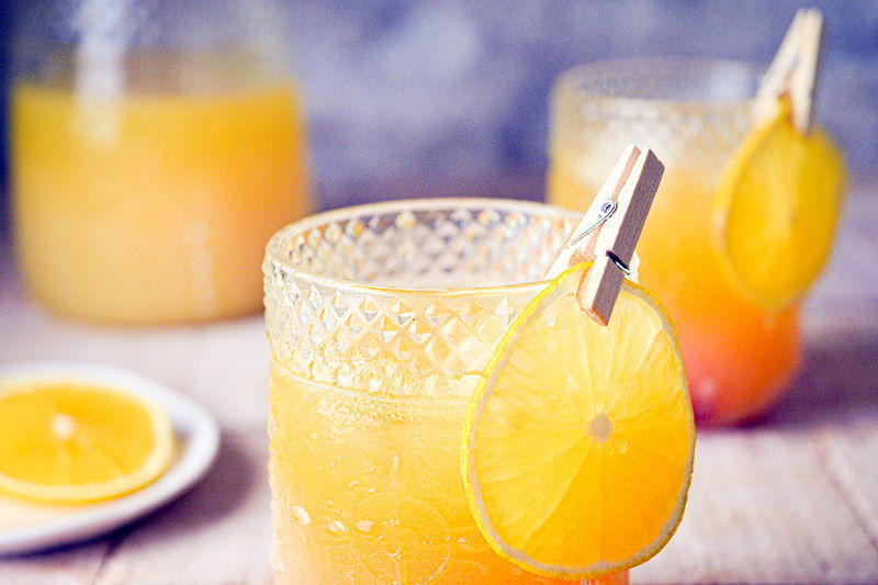 Fall Pumpkin Party Punch in a clear glass with a thin orange slice garnish clipped on with a clothespin.