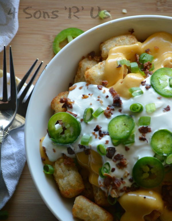 Jalapeno popper totchos in a white bowl, wooden background.