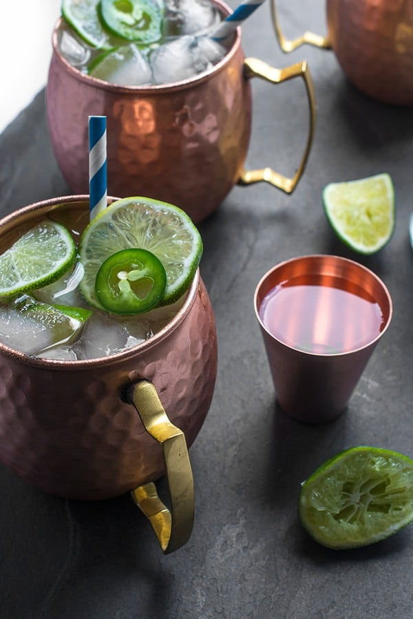 Moscow mule in copper mugs with limes slices and jalapeno slices scattered around.