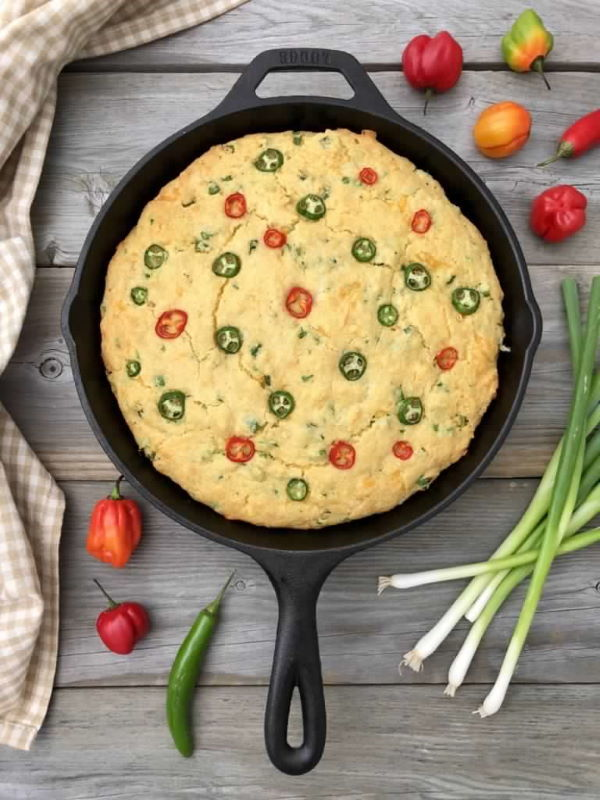Cornbread in a cast iron skillet, green onion on the side on wooden background.