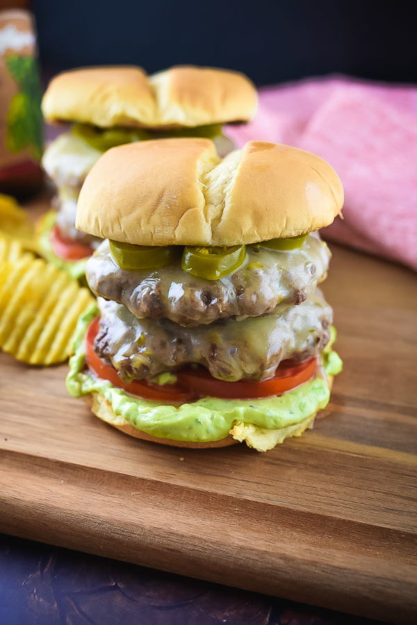 Spicy jalapeno double cheese burger on a wooden cutting board.