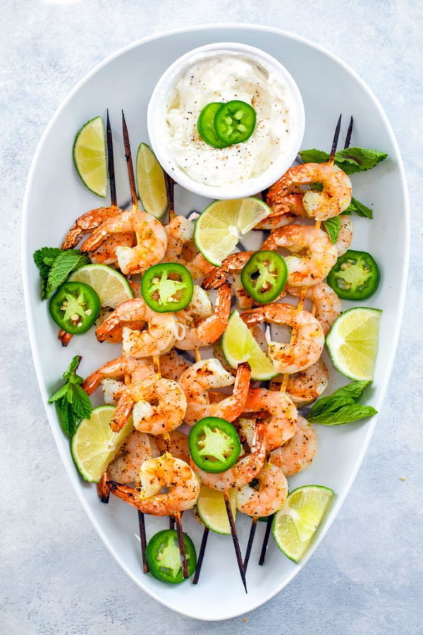 Tequila jalapeno shrimp skewers with a small bowl of dip on white serving dish.