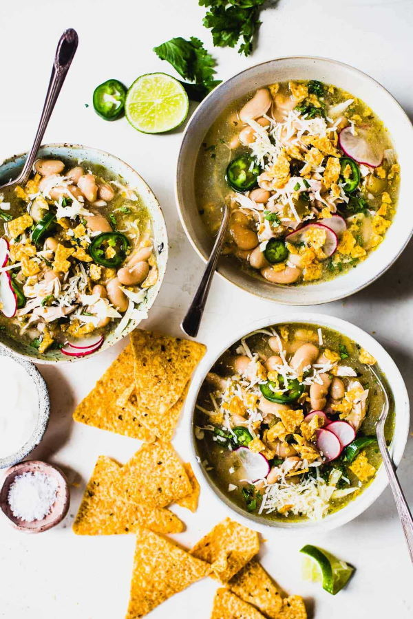 Jalapeno chicken soup in three white bowls with spoons, tortillas on the side.