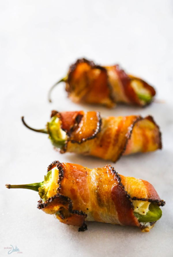Jalapeno popper wrapped in bacon, white background.
