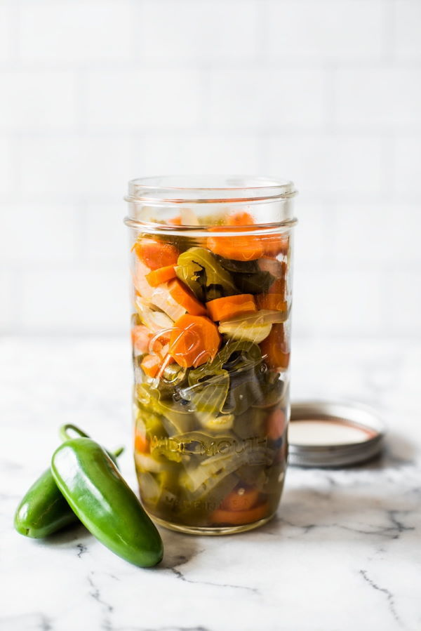 Mexican pickled jalapenos in a jar, jalapenos on the side, marble background.