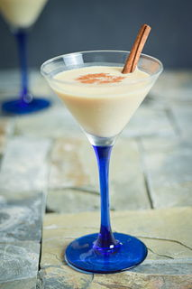 Brandy Alexander in a blue and clear martini glass, with cinnamon stick, on tile.