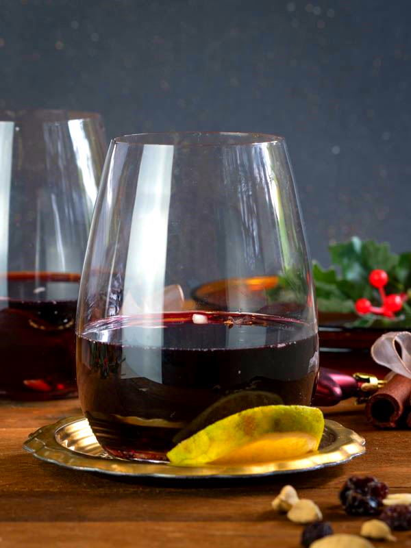 Cinnamon orange glogg in 2 glasses, almonds on the side, wooden background, cinnamon sticks wrapped in a bow.
