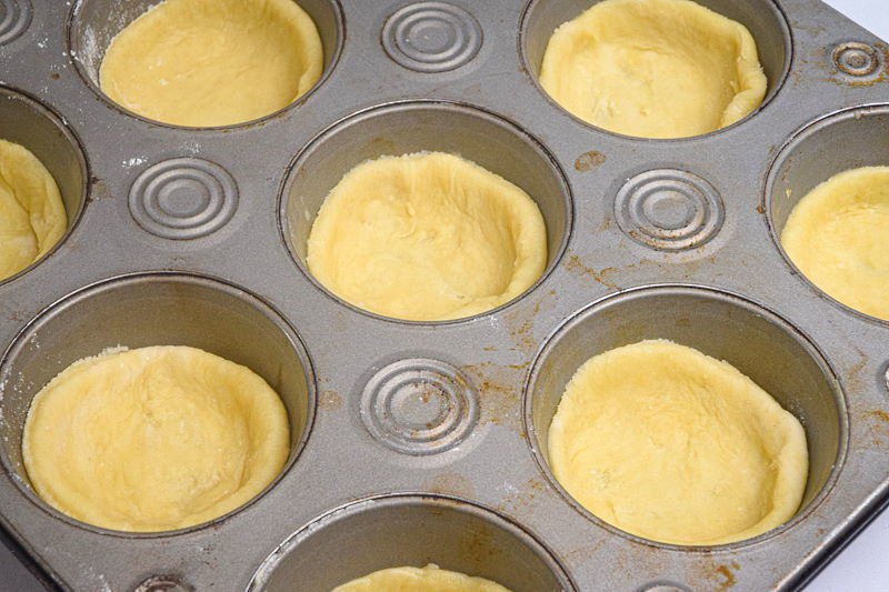 Dough discs in a muffin tray.