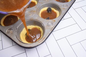 Butter tart mixture being poured into pastry in muffin tins.