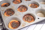 Baked butter tarts in a muffin tin.