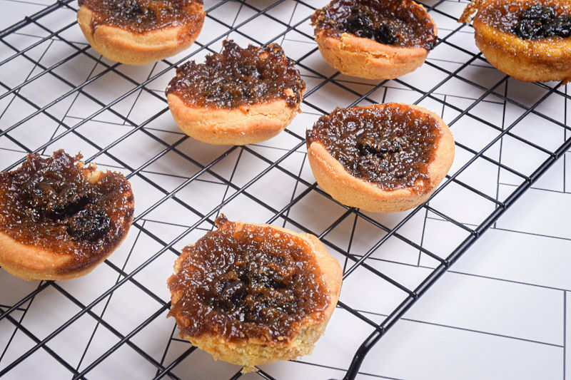 Baked butter tarts on a baking rack.
