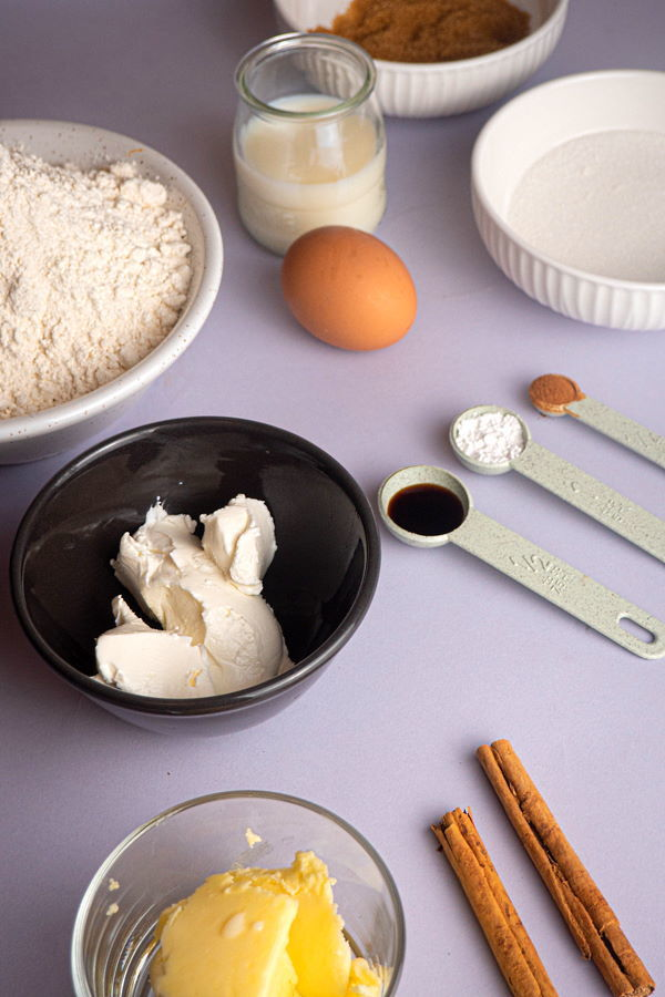 Cinnamon bun ingredients prepped on white background.