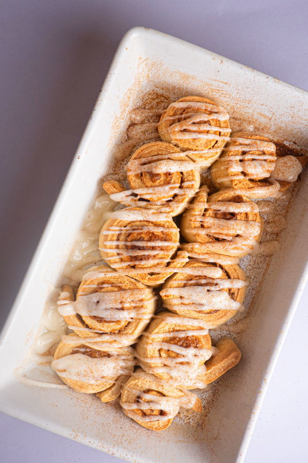 Cinnamon Buns with cream cheese frosting drizzled on top in white serving dish.