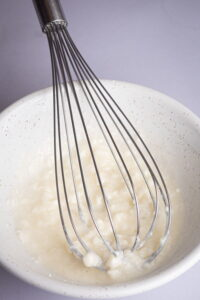 A bowl with flour mixture and whisk.