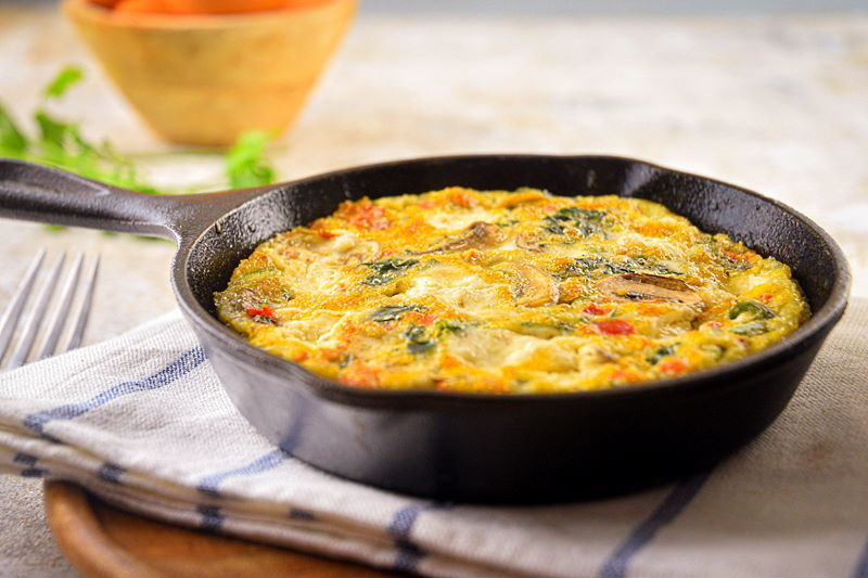 Electric Skillet Vegetable and Goat Cheese Frittata on a pie server and in a cast iron pan.