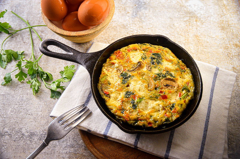 Electric Skillet Vegetable and Goat Cheese Frittata in a cast iron pan, with eggs, fork and cilantro on the side.