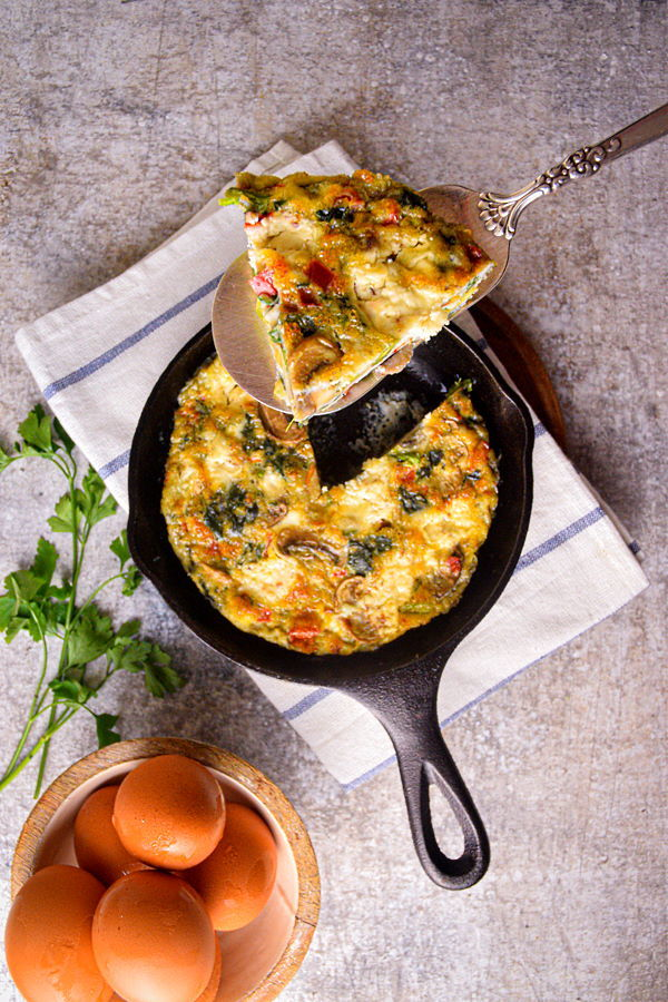 A piece of Electric Skillet Vegetable and Goat Cheese Frittata on a pie server and in a cast iron pan, with eggs and cilantro on the side.