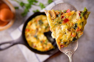 A piece of Electric Skillet Vegetable and Goat Cheese Frittata on a pie server.